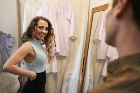 changing room: Man watches his partner trying on clothes in changing room Stock Photo