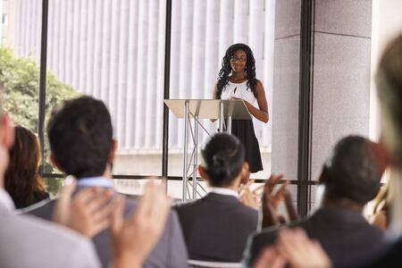 lectern: Audience at seminar applauding young black woman at lectern