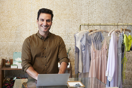 Young man working in clothes shop using laptop at counter Stock Photo
