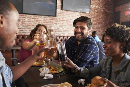 barra de bar: Amigos Comer en Sports Bar Con pantallas en el fondo