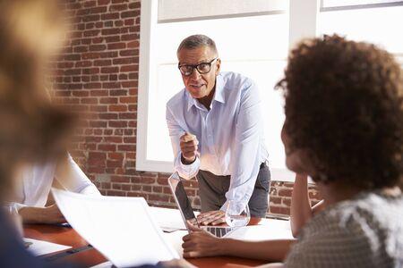 addressing: Mature Businessman Addressing Boardroom Meeting