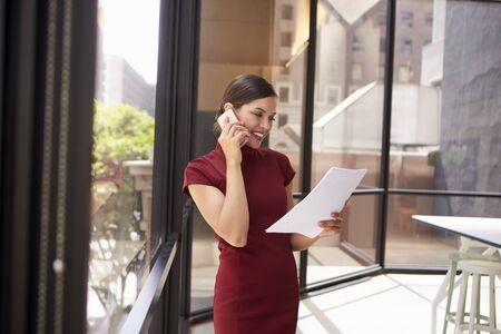 personas de pie: Sonriente mujer blanca en el teléfono en la oficina mirando el documento