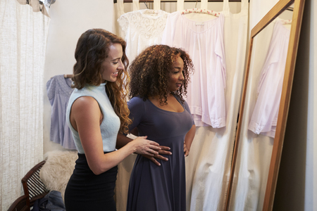 Woman in boutique changing room with friend trying on dress Stock Photo