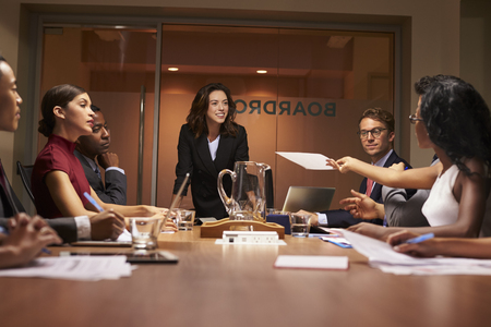 Colleague passing document at a business meeting, low angle Stock Photo