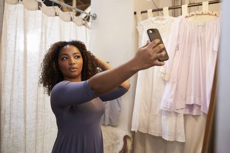 changing room: Woman taking selfie in a boutique changing room