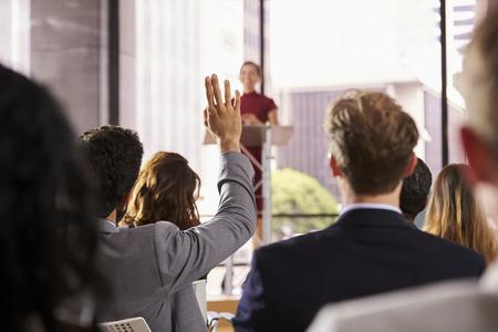 Presentator bij business seminar neemt een vraag van het publiek Stockfoto