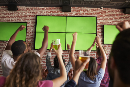 Rear View Of Friends Watching Game In Sports Bar On Screens Stok Fotoğraf