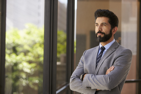 man looking out: Middle aged Hispanic businessman looks out of office window Stock Photo