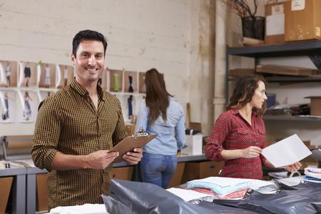 De Spaanse mens pakt orden voor distributie in, glimlacht naar camera Stockfoto
