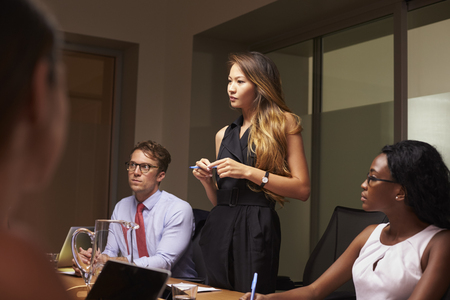 Businesswoman stands among seated team at an evening meeting