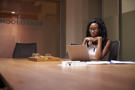 Young black businesswoman working late alone in office Stock Photo