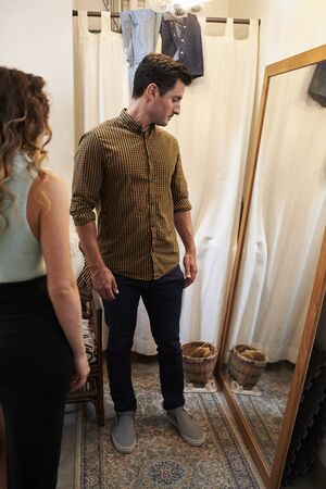 changing room: Partner and man trying on clothes in changing room, vertical Stock Photo