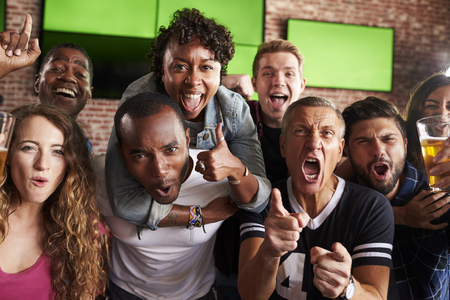 sports bar: Portrait Of Friends Watching Game In Sports Bar On Screens Stock Photo