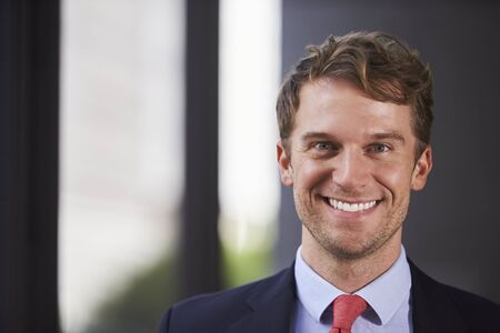 Young white businessman smiling, close up
