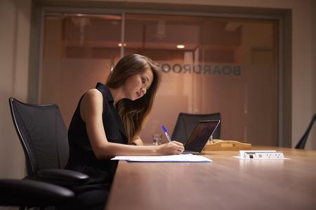Joven empresaria asiática trabajando solo tarde en una oficina