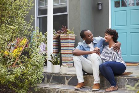 若いカップルは、家の外の互いを見て座る 写真素材