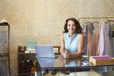 Jovem mulher que trabalha na loja de roupas inclinando-se no contador