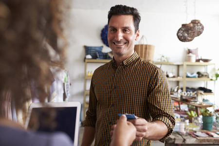 Man paying sales assistant with credit card in clothes shop