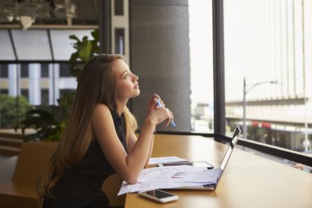 Donna di affari che lavora in un ufficio che osserva fuori dalla finestra Archivio Fotografico