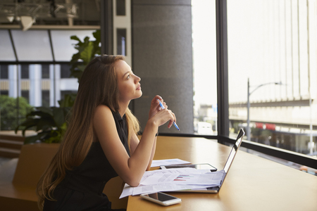 Businesswoman working in an office looking out of the window Standard-Bild