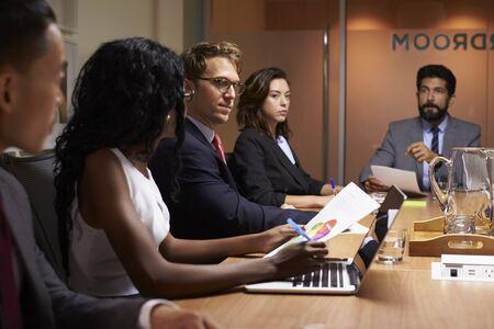 Geschäftsleute bei einer Abendsitzungssitzungssitzung, Abschluss oben