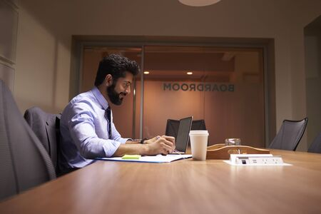 Middle aged Hispanic businessman working late in an office Stock Photo