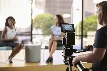 foreground focus: Two young women on set for TV interview, focus on foreground Stock Photo