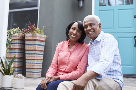 american house: Senior couple sit on steps outside their house, close up
