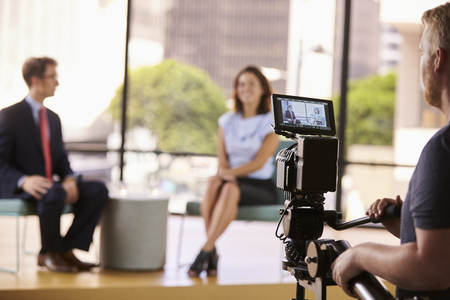 Man and woman on set for a TV interview, focus on foreground