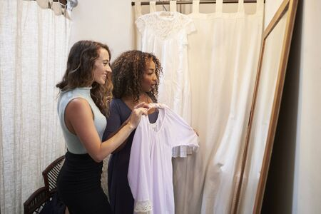 changing room: Woman in boutique changing room with friend holding a dress
