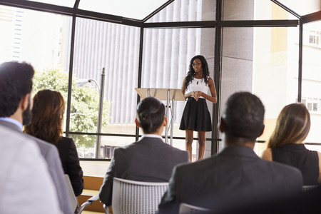 presenting: Young black businesswoman presenting seminar to an audience