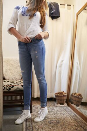 changing room: Woman trying on jeans in a changing room looking in mirror