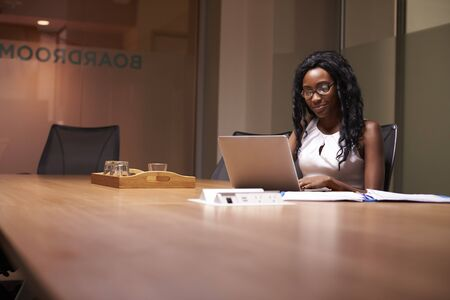 working late: Young black businesswoman working late on laptop in office