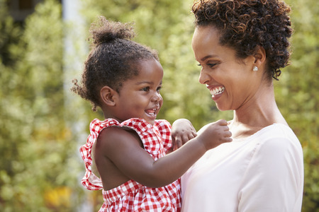 Young African American mother holds baby daughter in garden