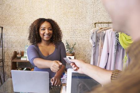 Assistent bij kledingwinkel die creditcard van klant neemt