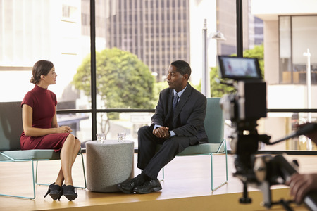 Black man and white woman on set filming a TV interview Stock Photo