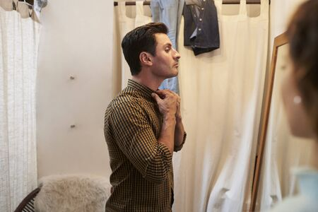 changing room: Woman watches her partner trying on shirt in changing room
