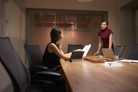 late 20s: Businesswoman stands talking to colleague working late