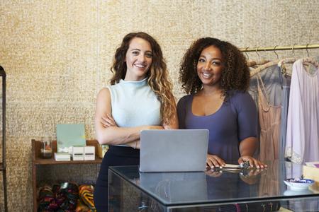 Twee vrouwen werken in kleding winkel kijken naar camera Stockfoto