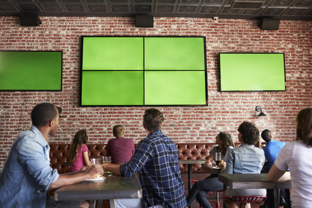 Rear View Of Friends Watching Game In Sports Bar On Screens Banco de Imagens