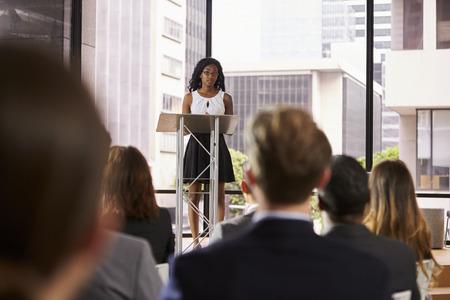 Jonge zwarte vrouw bij katheder presenteren seminar aan publiek Stockfoto
