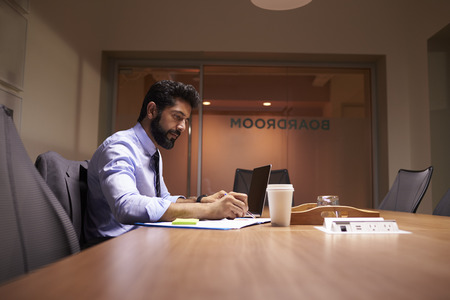working late: Middle aged Hispanic businessman working late in an office Stock Photo
