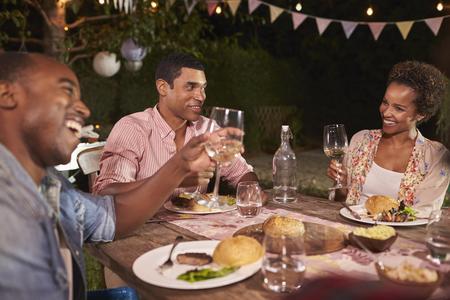 anochecer: Tres jóvenes adultos de raza negra que disfrutan de una cena de jardín