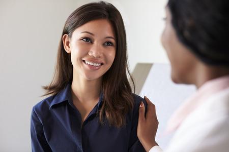 Femme Réunion de Doctor With Patient En salle d'examen Banque d'images - 71352606