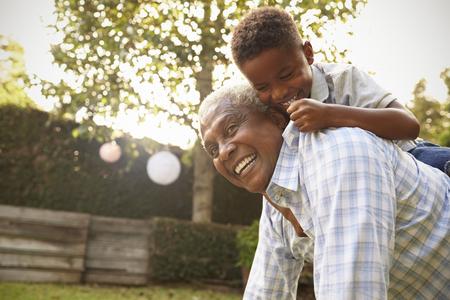 그의 할아버지에 등산 젊은 흑인 소년? 정원에 다시 스톡 콘텐츠