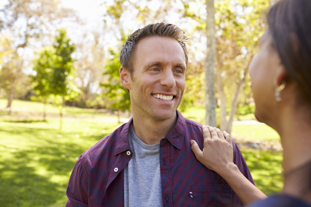 Mixed race couple in a park looking at each other