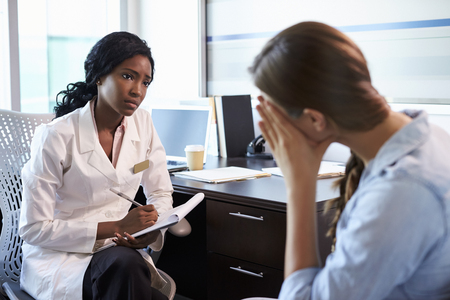 Doctor In Consultation With Depressed Female Patient Stock Photo