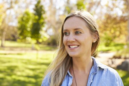mid thirties: Mid thirties white woman looking away from camera in park