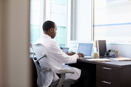 bata blanca: Doctor Wearing White Coat Working On Laptop In Office