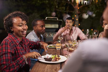 성인 흑인 가족은 저녁 식사와 대화를 정원에서 즐깁니다.